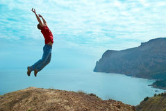 Man jumping cliff. Against sea and mountain with blue sky Stock Photos
