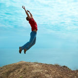 Man jumping cliff. Against sea and mountain with blue sky Stock Photo