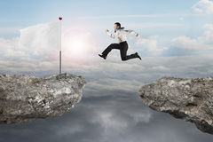 Man jumping on cliff with blank flag and sunlight cloudscapes Royalty Free Stock Images