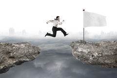 Man jumping on cliff with white flag and cloudy cityscape Royalty Free Stock Photos