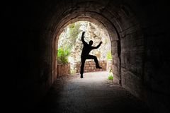 Man jumping in a dark tunnel. Silhouette of a man jumping in a dark tunnel on the walking path in Petrovac bay,Montenegro stock photo