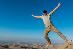 Man jumping in the desert of the peruvian coast at Stock Image