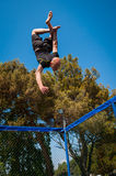 A man trick jumping on a trampoline. A man jumping and doing tricks on a tranpoline or canvas Royalty Free Stock Photography