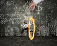 Man jumping through fire circle hand holding with doodles wall Royalty Free Stock Photos
