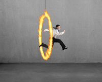 Man jumping through fire hoop with concrete wall Royalty Free Stock Image