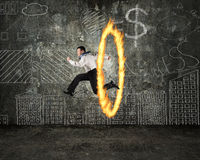 Man jumping through fire hoop with doodles wall stock image