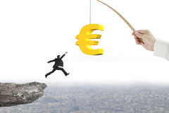 Man jumping golden euro symbol fishing lure with cliff cityscape Stock Image