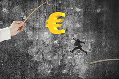 Man jumping golden euro symbol fishing lure mottled concrete wal Royalty Free Stock Photography
