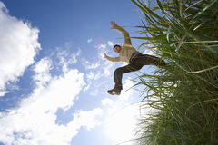 Man jumping from grass outdoors, low angle view Royalty Free Stock Photo