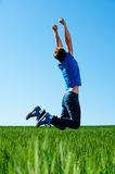 Man jumping on the green field Stock Image