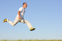Man jumping on green field Stock Photos