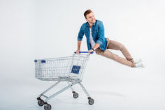 Man jumping and having fun with shopping trolley on white. Excited young man jumping and having fun with shopping trolley on white Royalty Free Stock Photo