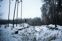 Man jumping on hill in winter forest Royalty Free Stock Images