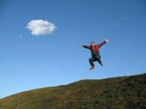 Man jumping on hillside royalty free stock image