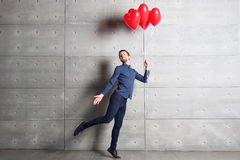 Man jumping indoors on background gray wall with red heart shaped balloons Royalty Free Stock Images