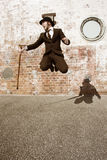 Man Jumping For Joy. A Happy Man In A Black Suit With Bowler Hat And Cane, Jumping For Joy Stock Images