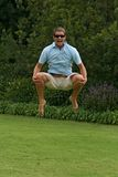 Man jumping with joy. Happy man, jumping in air, holding legs with happy face Royalty Free Stock Photography