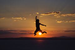 Man jumping by joy and happines on sunset stock images