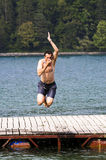 Man jumping into the lake. Outdoor image of man jumping into lake stock photography