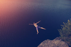 Man jumping into the lake from cliff royalty free stock images