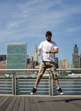 Man jumping and looking at his watch in New York. Man jumping and looking at his watch with Lower Manhattan in the background new york rush hurry river landscape stock photos