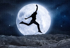 Man jumping in the moonlight Royalty Free Stock Photos