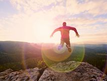 Man jumping from the mountain edge.  Man jumping off a cliff without rope. Risky moment. Rough rocky ground Stock Images