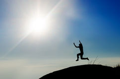 Man jumping on mountain peak at bright sky Royalty Free Stock Photos