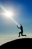 Man jumping on mountain peak silhouette Stock Photography
