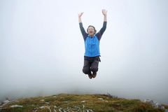 Man jumping on mountain peak Stock Images