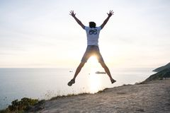 Man jumping on a mountain road with seascape at sunset. Back view Stock Photo