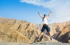 Man jumping on the mountain top. With a view Stock Images