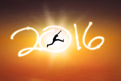 Man jumping with numbers 2016 on the sky. Silhouette of young man jumping on the sky while celebrating new year 2016 at sunset time Royalty Free Stock Photos
