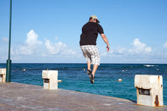 Man jumping into the ocean Royalty Free Stock Image