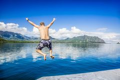 Man jumping into the ocean while on a beautiful scenic Hawaiian vacation royalty free stock image