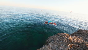 Man jumping off of the cliff and dives into the Mediterranean sea