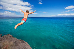 Man jumping off cliff into the ocean. Summer fun lifestyle Stock Photography