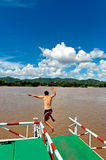 Man jumping off river raft into water. Of the Mei Kong river royalty free stock photography