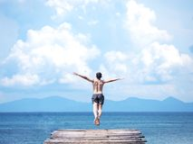 Man jumping off wooden bridge into blue sea. stock images