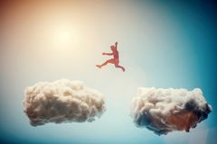 Man jumping from one cloud to another. Challenge. Man jumping from one cloud to another. Taking risks and challenge concept. Overcoming problems, winning royalty free stock photography