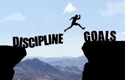 Man jumping over abyss with text DISCIPLINE/GOALS. In front of mountain background stock photos