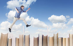 Man jumping over books Royalty Free Stock Photos