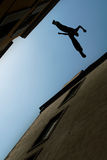 Man jumping over building roof vertical image Stock Photo
