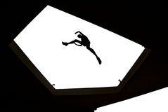 Man jumping over building roof on white background Stock Images