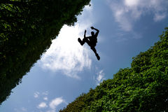 Man jumping over bushes Stock Images