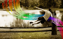 Man jumping over the fence on the rainbow. In summer stock images