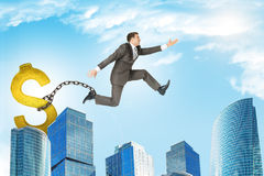 Man jumping over gap with dollar sign ballast Royalty Free Stock Images