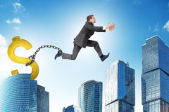 Man jumping over gap with gold dollar ballast Stock Photography