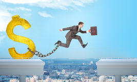 Man jumping over gap with gold dollar sign ballast Stock Photography
