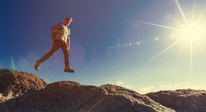 Man jumping over gap on mountain hike Stock Images